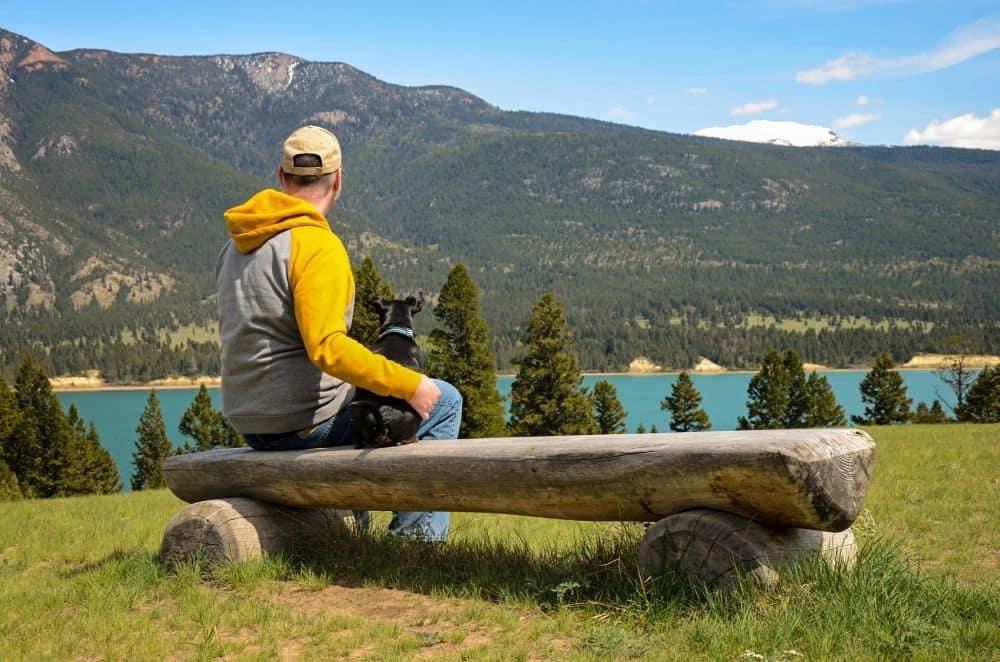 Mann und Zwergpinscher auf einer Bank vor einem See