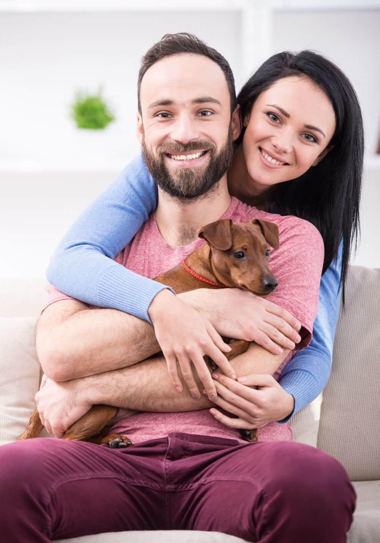Junges Paar mit Zwergpinscher Welpen im Arm